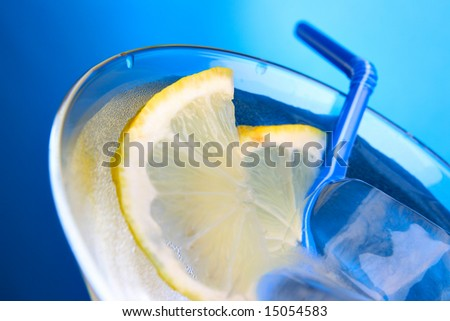 Cocktail glass with ice cubes and lemon slice close-up viev from above - stock photo