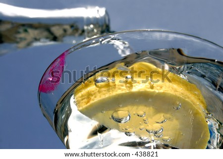 Cocktail glass with lipstick and bottle poring liquid - stock photo