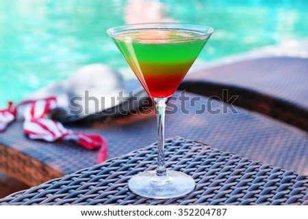 Cocktail on swimming pool background - stock photo
