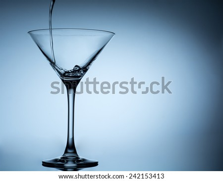 cocktail pouring in martini glasses close up - stock photo