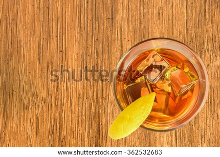 Cocktail, right, with Lemon on bamboo board - stock photo