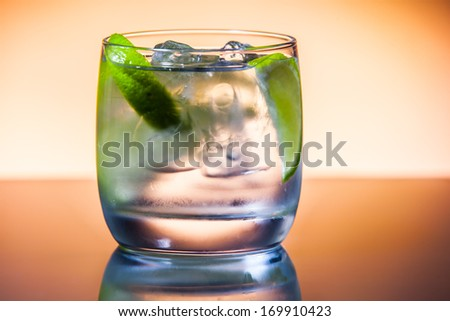 cocktail served on a dark bar top garnished with a lime - stock photo