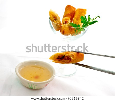 cocktail springroll, one cut piece is being dip in sweet plum sauce - stock photo