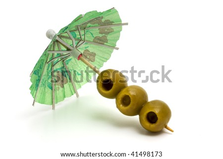 Cocktail umbrella and olives. Isolated - stock photo