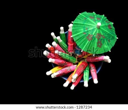 Cocktail umbrellas (isolated against black) - stock photo