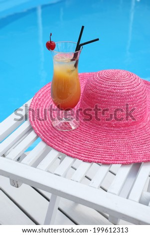 cocktail with cherry on a beach table with a straw hat near the swimming pool - stock photo