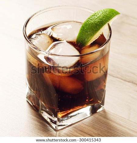 Cocktail with cola and ice on wooden table. in a glass with a cocktail, put a slice of lime