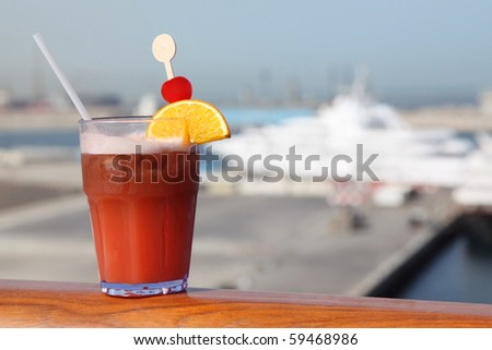 cocktail with fruits in glass on ship deck rail, port with cruise liner on background - stock photo