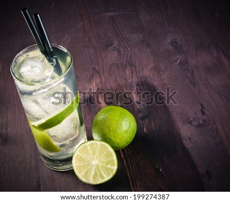 Cocktail with ice and lime slice isolated on old wood table and space for text - stock photo