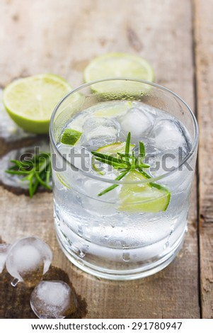 Cocktail with ice and lime slice on wooden background - stock photo