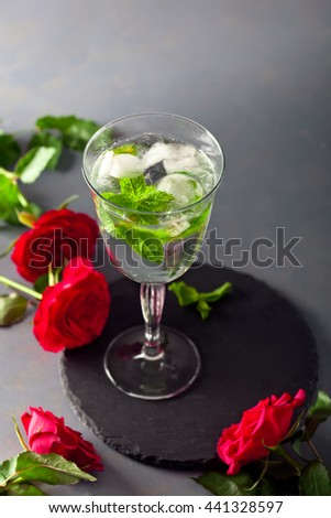 Cocktail with ice cubes and peppermint set with red roses. Valentine day, celebration and chill out concept. - stock photo