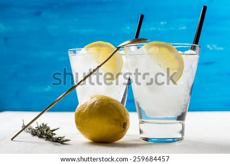 Cocktail with lemon and ice in a glass on the white wooden table - stock photo
