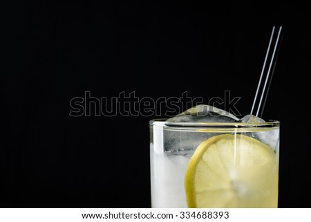 Cocktail with lemon and ice on the black background - stock photo