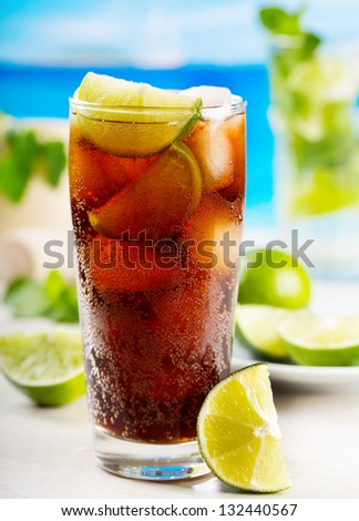 cocktail with lime and Cola on beach - stock photo