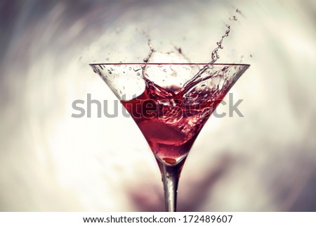 Cocktail with liquid splashing out - stock photo