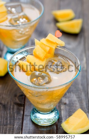 Cocktail with mango fruit on wooden table top - stock photo