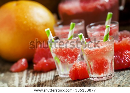 Cocktail with vodka, soda and grapefruit with striped straws, selective focus - stock photo