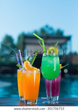 Cocktails by the pool with sparkling blue water - stock photo