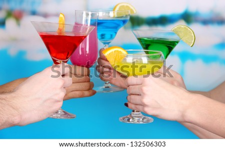 Cocktails in hands on pool background - stock photo