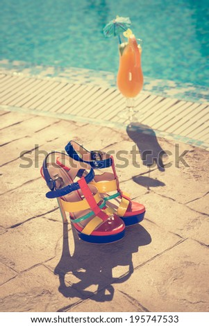 Cocktails near the swimming pool with high-heel shoes - stock photo
