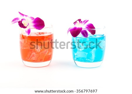 Cocktails red and blue with beautiful flower decorations in cocktail glasses on white background - stock photo