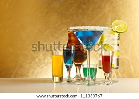 Cocktails with alcohol on grungy gold background - stock photo