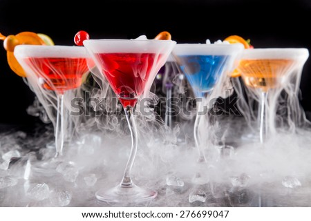 Cocktails with ice vapor on bar desk, close-up. - stock photo