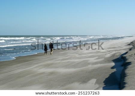 Cocoa Beach, Florida, USA - February, 2015. People walking along the beach on a windy day. Atlantic ocean. Florida. USA - stock photo
