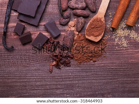 Cocoa beans, powder, chocolate and spices on the wooden table, top view - stock photo