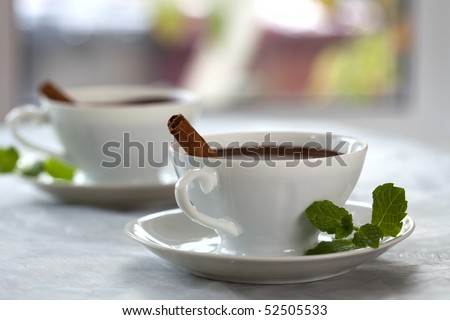 cocoa chocolate in white cups with cinnamon sticks and mint leaves, shallow DOF - stock photo