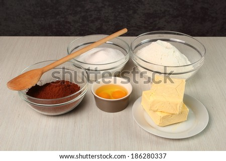 Cocoa, Flour, Sugar, Egg and Butter - Ingredients to make chocolate cookies. Making Chocolate Cookies. - stock photo