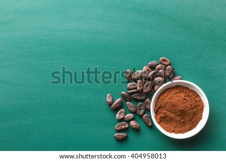 cocoa powder and cocoa beans on chalkboard - stock photo