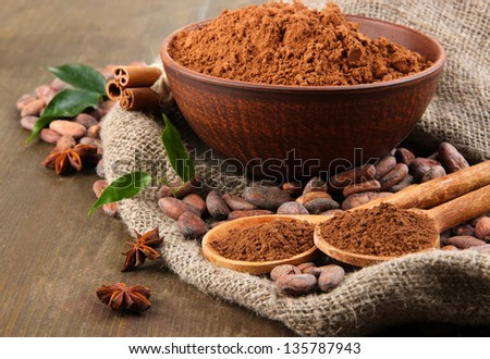 Cocoa powder and cocoa beans  on wooden background - stock photo