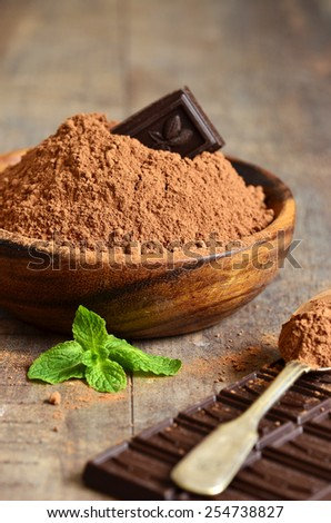 Cocoa powder in a wooden bowl. - stock photo