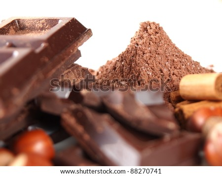 cocoa powder mountain, chocolate bars, nuts, vanilla - stock photo