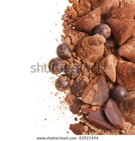cocoa powder with chocolate truffles isolated against white background - stock photo