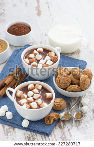 cocoa with marshmallows and almond cookies on white wooden table, top view, vertical - stock photo