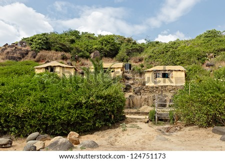 Cocohut from wood and palm leaves on the seashore. - stock photo