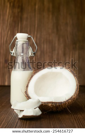 coconut and milk in a glass bottle on wooden - stock photo
