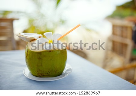 Coconut, beach cafe, plumeria on table with blurry background - stock photo
