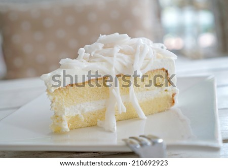 Coconut cake on white plate. - stock photo
