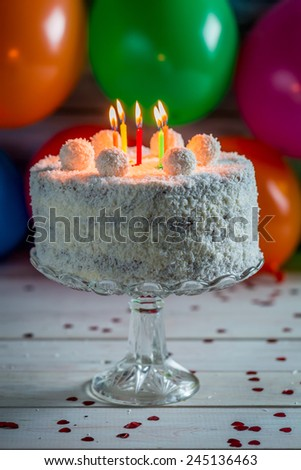 Coconut cake with candles on birthday - stock photo