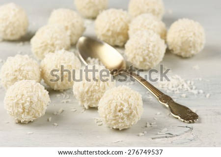 Coconut candies and spoon on wooden shabby background. Shallow DOF, focus on foreground. - stock photo
