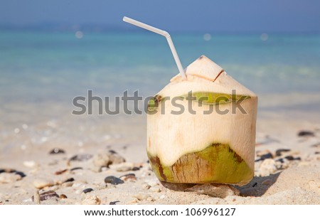 Coconut cocktail on the white sandy beach - stock photo