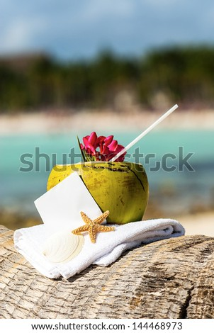 Coconut cocktail starfish tropical Caribbean beach refreshment and towel - stock photo