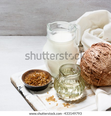 Coconut, coconut milk, sugar and oil on the white wooden table. Ingredients. Organic food concept. Still Life - stock photo