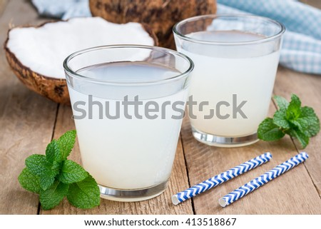 Coconut drink with pulp in glass on wooden table - stock photo