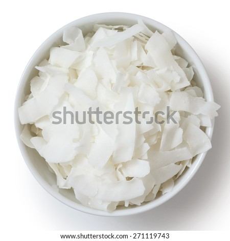 Coconut flakes in white ceramic bowl. From above. - stock photo
