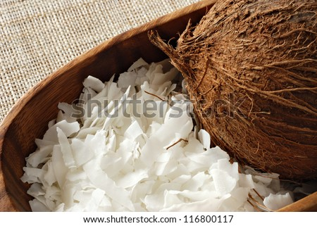 Coconut flakes with whole coconut in wooden bowl.  Macro with shallow dof. - stock photo