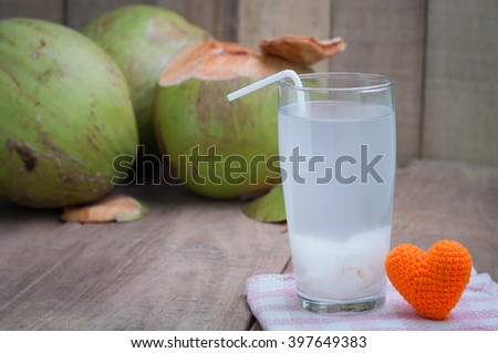 Coconut juice and group of coconut on wood floor. - stock photo